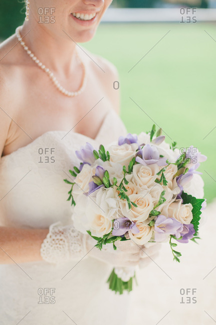 Bride in lace gloves holds bouquet of flowers