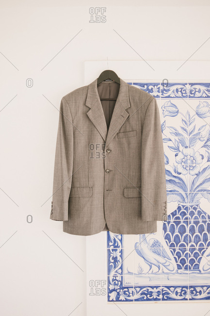 Suit jacket hanging in front of painted tile