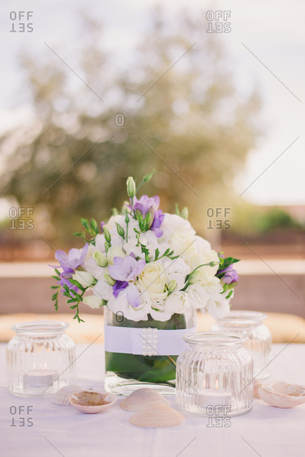 Table with centerpiece of seashells, candles and white and purple flower arrangement