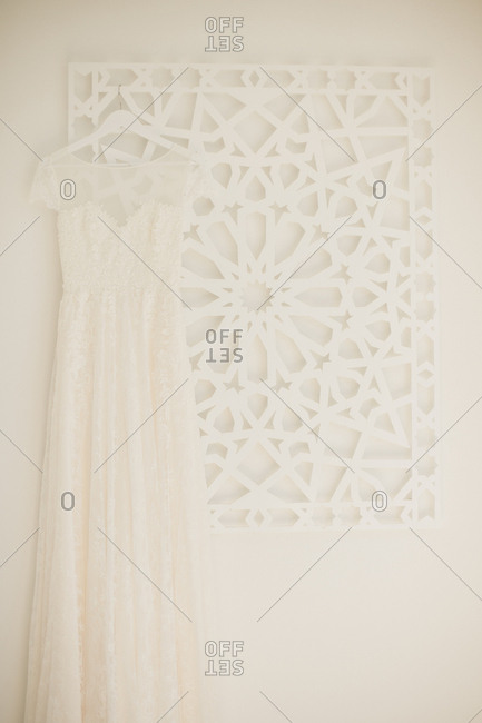 Wedding dress hanging from white wall decoration