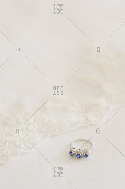 Ring with three blue stones on white background with lace