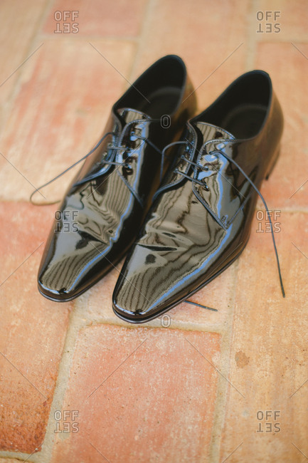 Shiny patent leather men's dress shoes on brick floor