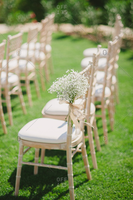 Baby's breath tied to chair at outdoor wedding