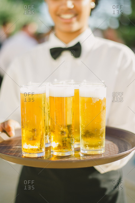 Server holding tray containing glasses of beer