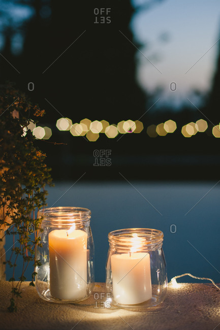Glass jars with lit candles at outdoor party