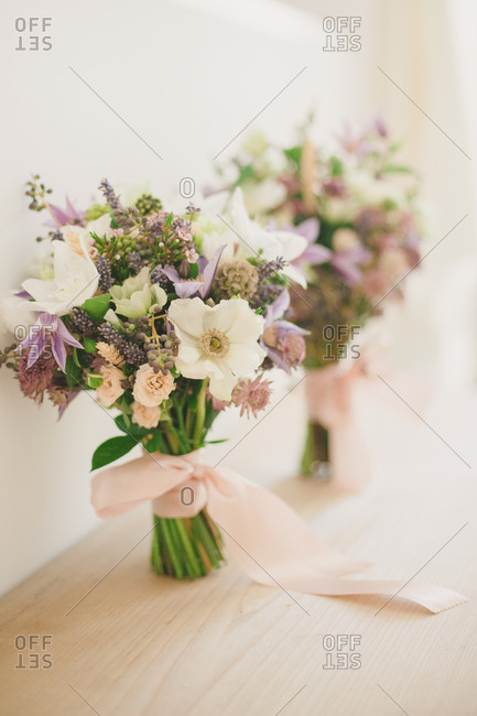 Fresh flower arrangements tied with pink ribbons