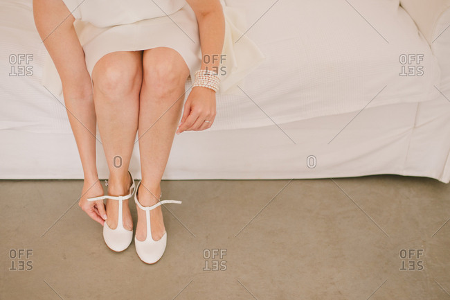 Woman in a white dress putting on strappy heels