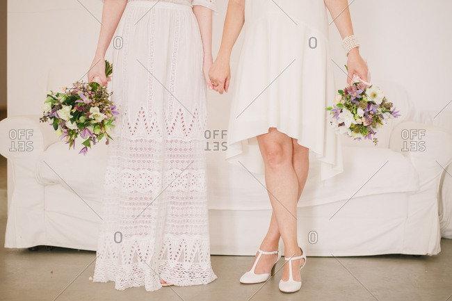 Two brides holding hands and holding bouquets