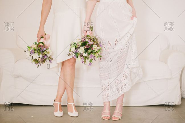 Two brides standing side by side holding bouquets