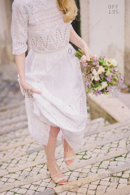 Woman holding a bouquet walking up stone steps