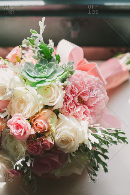 Bouquet of succulents and roses wrapped in pink ribbon