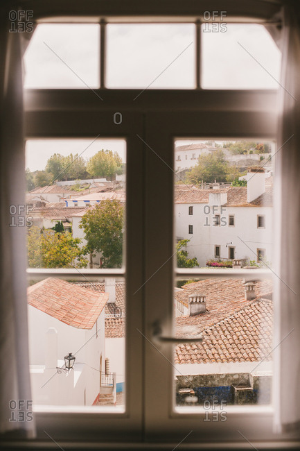 Tile rooftops seen through an upstairs window in Obidos, Portugal
