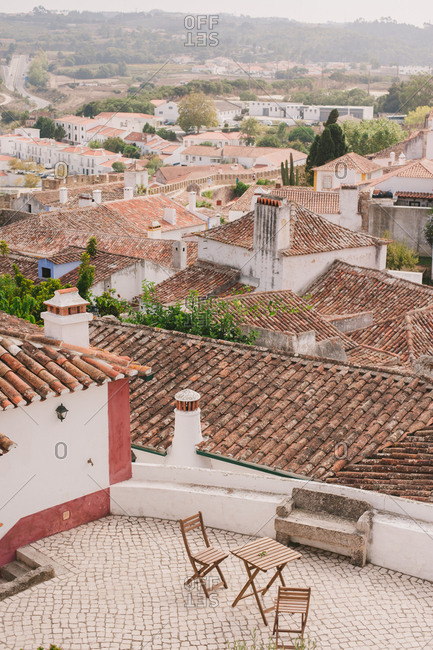 Cafe table and chairs overlooking tile rooftops in Obidos, Portugal