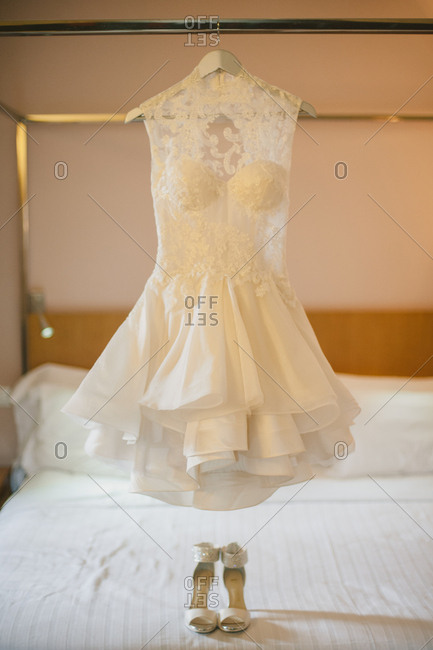 Short lace wedding dress hanging from a rack above strappy high heels
