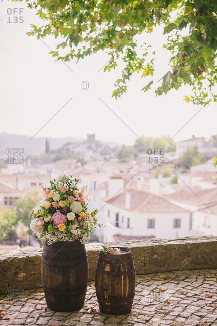 Floral arrangement on a rustic barrel overlooking the rooftops of Obidos, Portugal