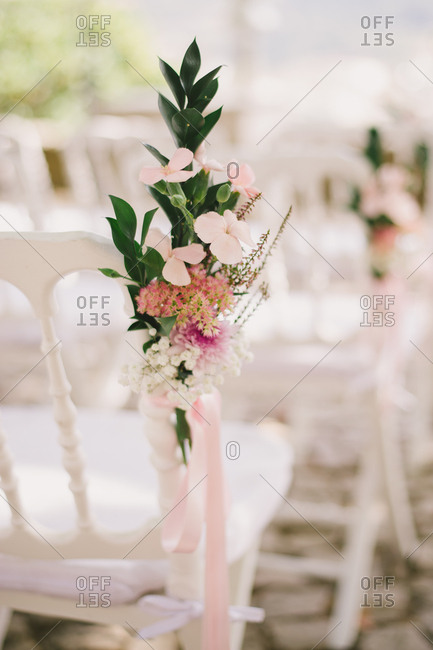 Floral arrangement on a white chair at a wedding