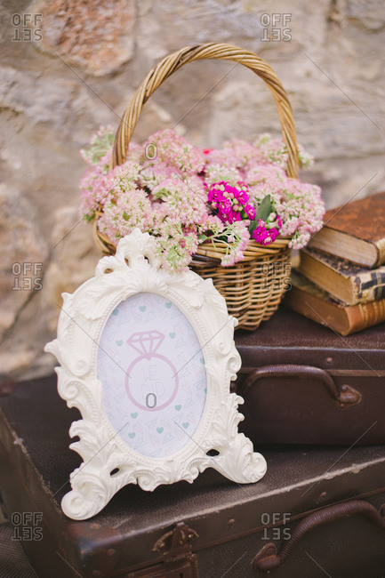 Picture frame with diamond ring on a stack of vintage suitcases