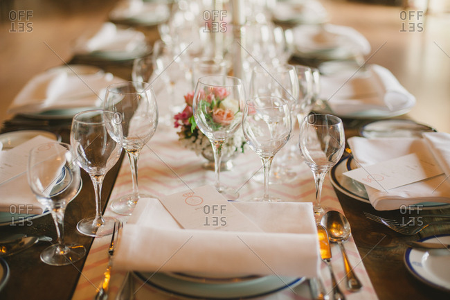 Glasses and place settings on a table for a wedding reception