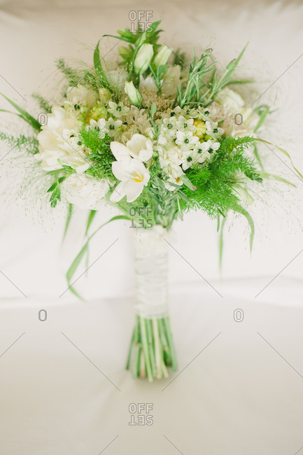 Green and white floral bouquet wrapped in ribbon