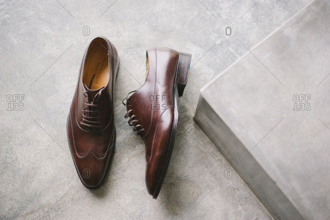 Man's brown leather formal shoes on a cement floor