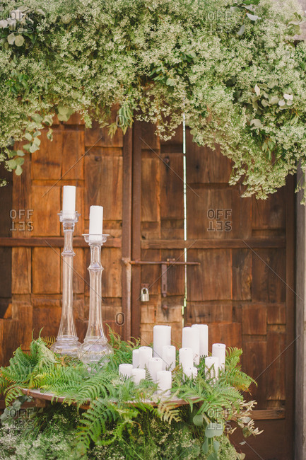 Candlesticks and ferns on a table need a rustic wooden doorway