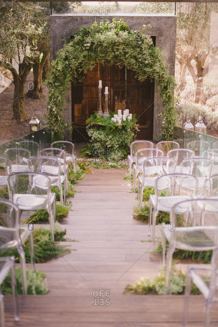 Modern seating at a wedding with a rustic wooden door and arbor