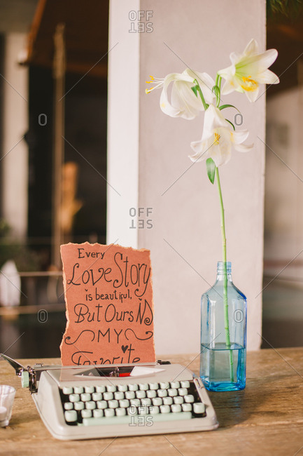 Retro typewriter with handwritten sign and flower in a glass bottle