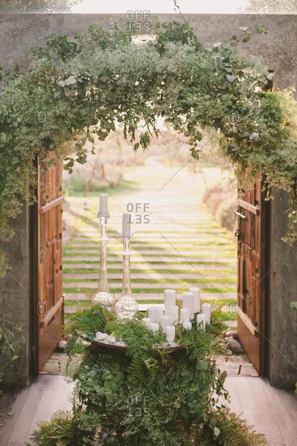 Open wooden doorways under an arbor leading into a garden
