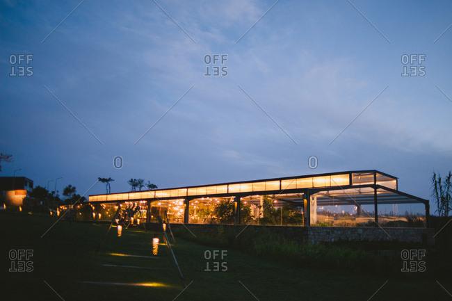 Modern greenhouse illuminated with lanterns at twilight