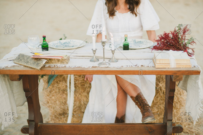 Bride sitting at a rustic table in a white dress and work boots