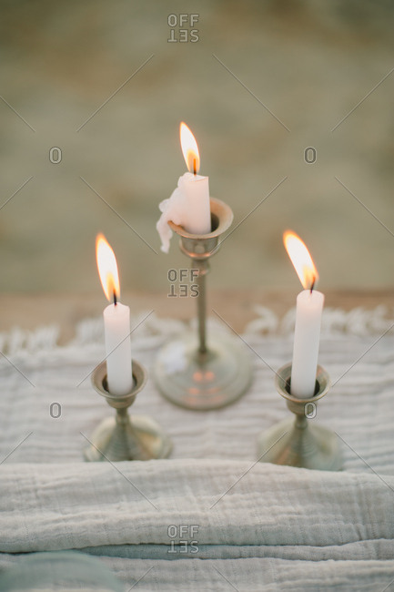 Old-fashioned pewter candlesticks and lighted candles