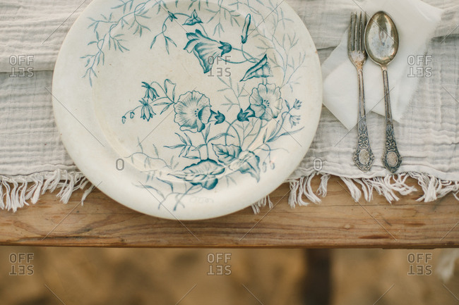 Plate with delicate blue floral pattern on a table with silverware