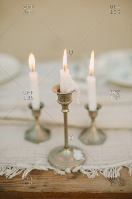 Three old-fashioned pewter candlesticks and lit candles