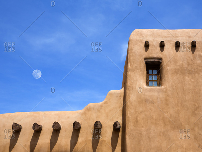 Adobe building under moon in blue sky, Santa Fe, New Mexico