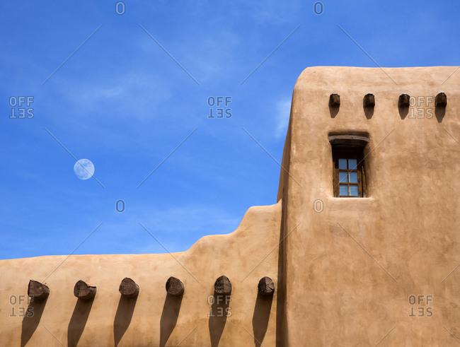 Adobe building under moon in blue sky, Santa Fe, New Mexico