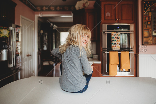 Little blonde girl sitting on kitchen counter looking back
