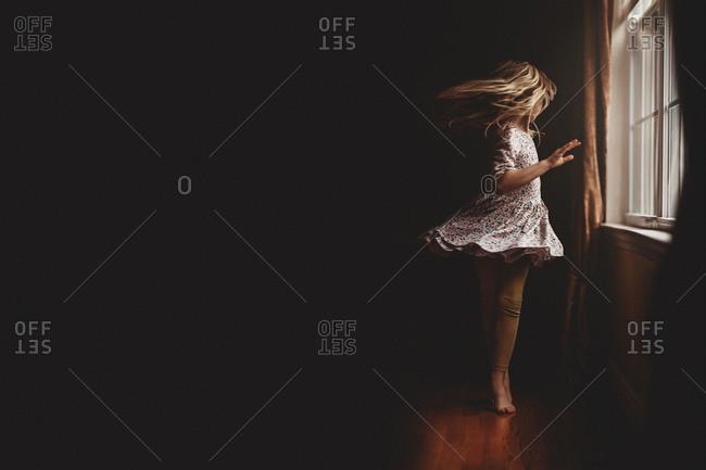 Girl dancing in window light