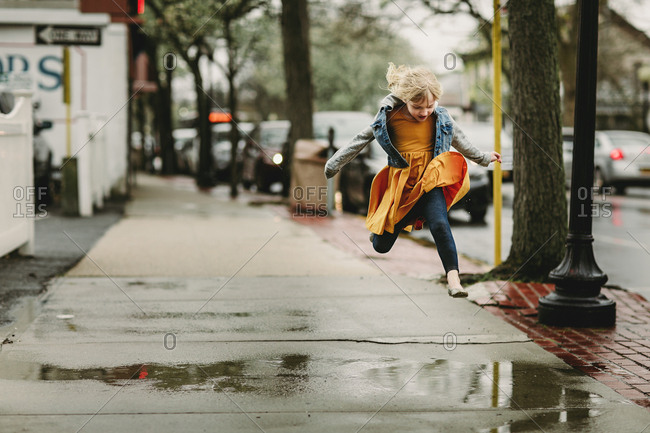 Girl leaping over a puddle on city street