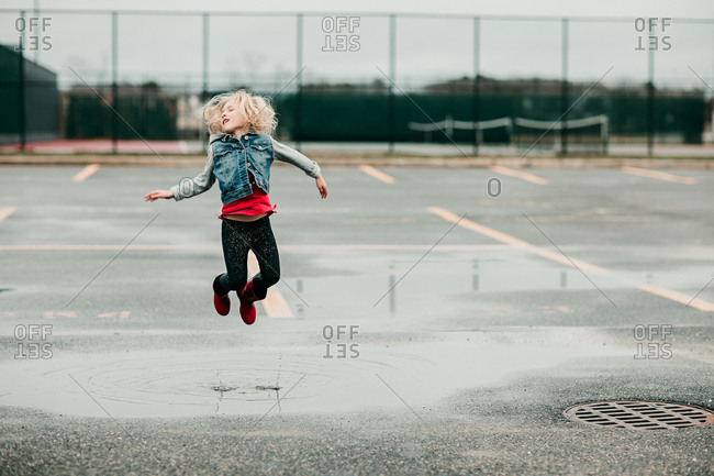 Girl leaping over a puddle in parking lot