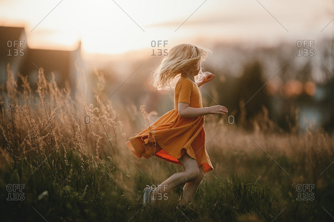 Blonde girl dancing in a field