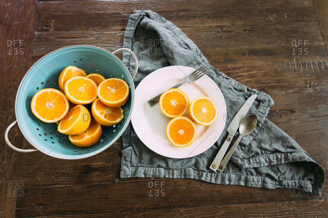 Oranges sliced on a plate and in a colander