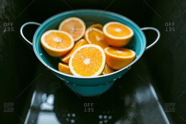 Orange halves in a colander