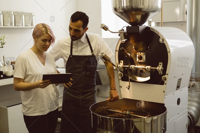 Male and female barista using digital tablet while standing besides coffee grinding machine in coffee shop