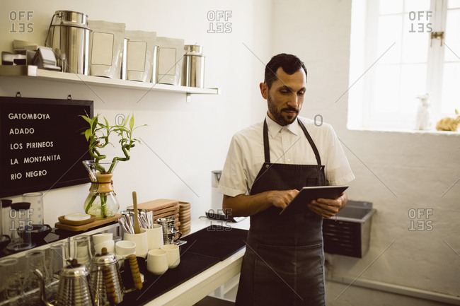Barista using digital tablet while standing besides coffee grinding machine in coffee shop