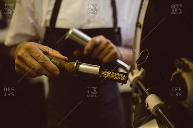 Barista pouring green coffee beans in coffee grinding machine in coffee shop