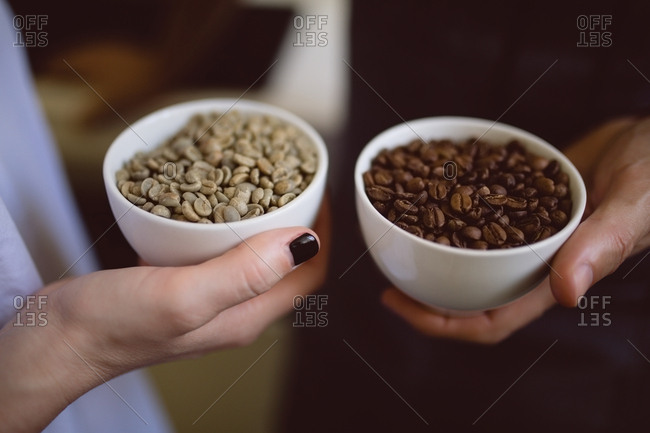 Male and female barista holding bowls of coffee beans in coffee shop