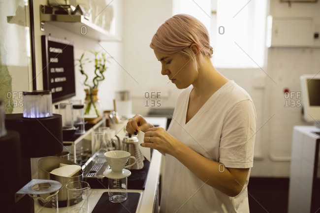 Female barista preparing filter funnel in coffee shop