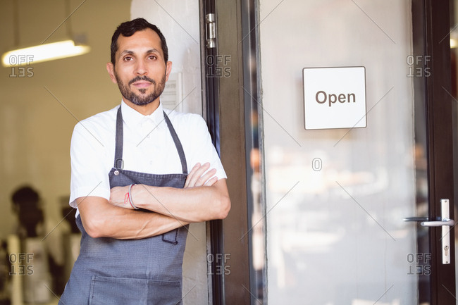 Portrait of barista standing with his arms crossed on coffee shop entrance
