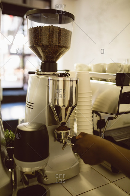 Hand of barista holding portafilter under coffee machine in coffee shop