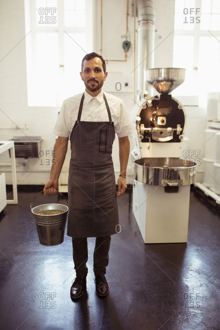 Barista holding bucket full of green coffee beans in coffee shop